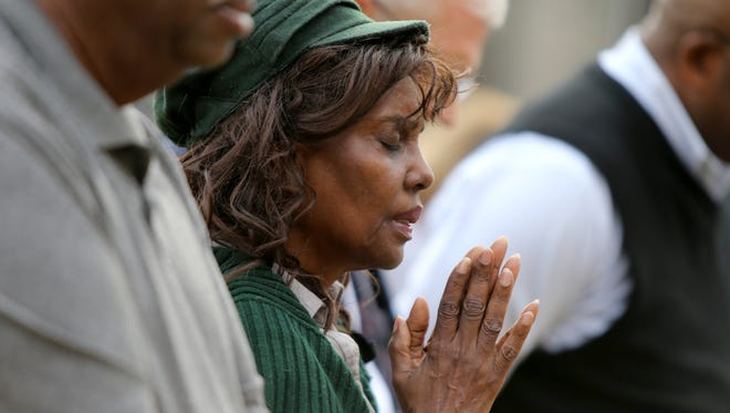 Evangelist Bernice Allen hold her hands in prayer outside Shelby County Juvenile Court as those in attendance pray for the juvenile providers and the people and families they serve.