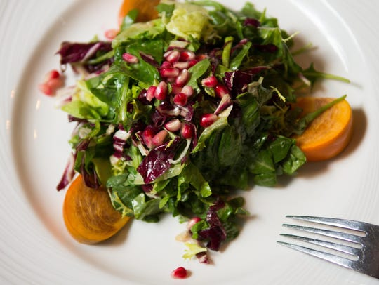 A starter salad comprises rocket, persimmon, pomegranate,