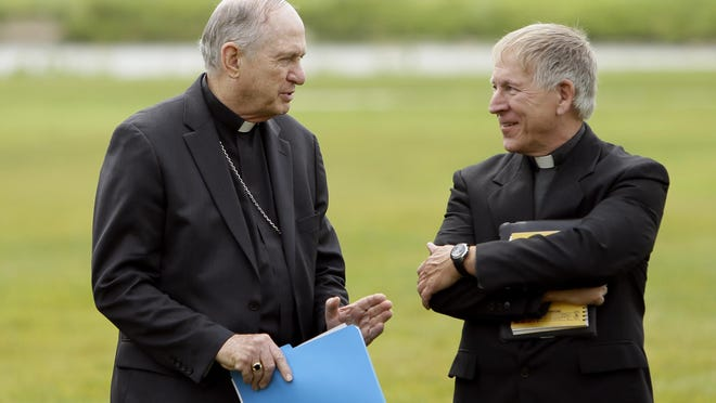 Bishop Richard Pates of the Diocese of Des Moines, talks with Father Bud Grant, right, during a news conference, Thursday, July 2, 2015, in Ankeny, Iowa. Roman Catholic leaders in Iowa are calling for presidential candidates to focus on the environment and income inequality in 2016. (AP Photo/Charlie Neibergall)