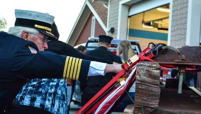 Bill Schwerdtfeger, a fire safety inspector, reaches to touch a beam that arrived at Poudre Fire Authority Station 4 on Saturday, Oct. 24, 2015. The donated beam from the World Trade Center was driven across the country by a team of PFA employees.