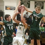 Enosburg's Calvin Carter, right and Caleb Laroche, left, team up to block a shot by Winooski's Sean Callahan during the second half of a boys basketball game last year.