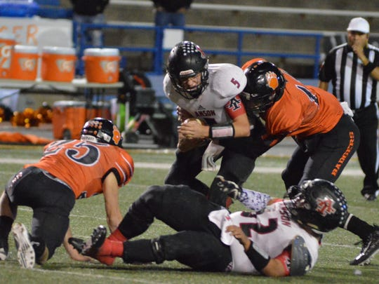 Anson quarterback Drew Hagler (5) is sacked by McCamey's Devin Wolfe with MHS' Andre Tone (25) and Anson's David Galvan (52) in the foreground.  McCamey defeated Anson 49-0 in a 2A Division I bi-district game in San Angelo on Saturday.