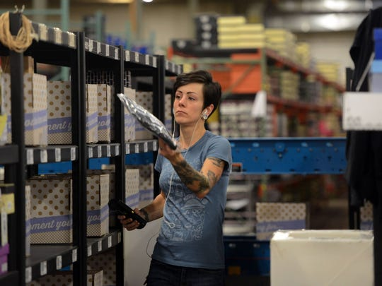 A warehouse worker moves merchandise in the Modcloth warehouse in Crafton, Pa., on Oct. 10.