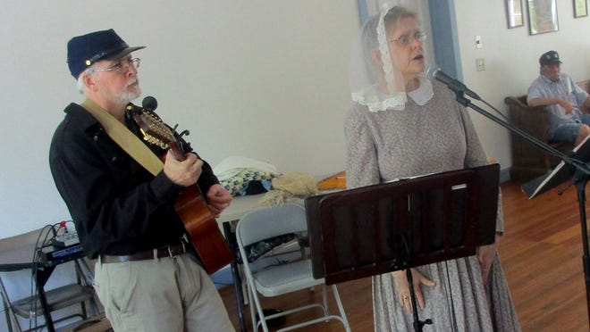 Guitarist David Hodges, left, and re-enactor Sandra Weber as Mary Brown perform a historical and musical set in June 2018 in the Smithfield Community Center. Local historian Dr. Milton Sernett is asking for the community's help in learning more about the building.