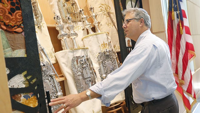 Rabbi Alfred Benjamin opens the torah cabinet in the sanctuary of Congregation Beth Shalom of the Blue Hills in Milton. Greg Derr/ The Patriot Ledger