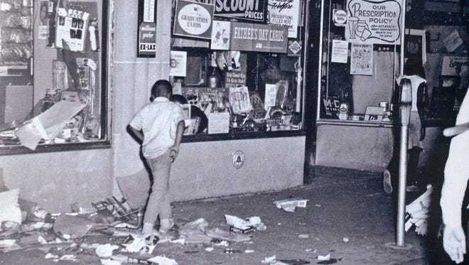 A child walks past a store looted by rioters in June 1967 in Cincinnati.