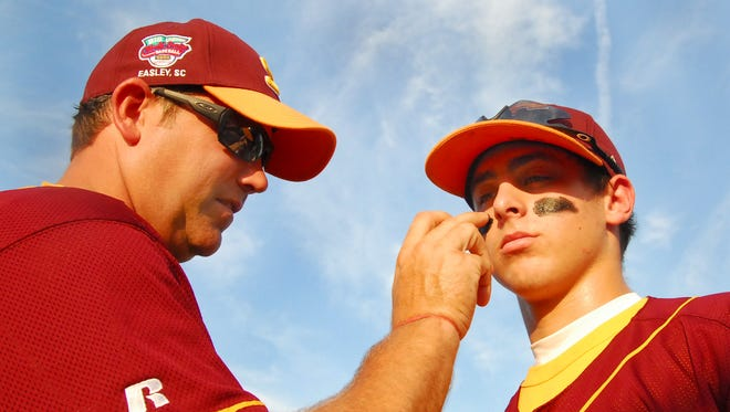 District 7 coach Jeff Young applies eye paint to one of his players, Colby Corn, before a 2008 Big League Baseball World Series Game in Easley. Young died Friday at the age of 49.