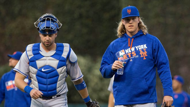 New York Mets starting pitcher Noah Syndergaard (right) and catcher Kevin Plawecki (left) walk across the field to begin the first inning against the Philadelphia Phillies at Citizens Bank Park Monday.