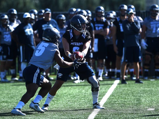 Nevada quarterback Ty Gangi (6) hands off to Jaxson