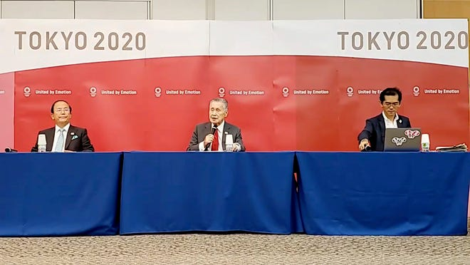 In this image made from video provided by Tokyo 2020 Official YouTube Channel, Tokyo 2020 Olympics President Yoshiro Mori, center, with CEO Toshiro Muto, left, attends a press conference after an IOC executive board meeting on Wednesday in Tokyo.