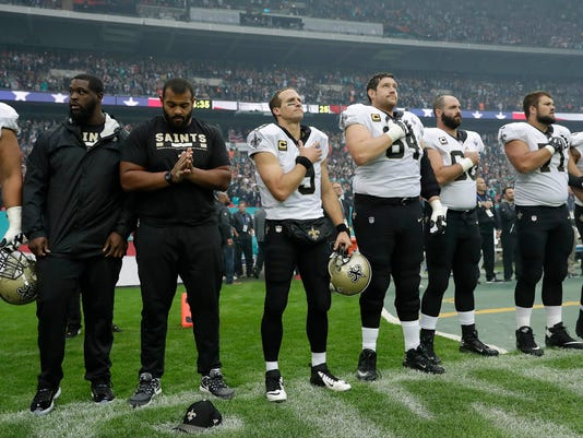 New Orleans Saints quarterback Drew Brees, center, stands with teammates for the U.S. national anthem ahead of an NFL football game against Miami Dolphins at Wembley Stadium in London, Sunday Oct. 1, 2017. (AP Photo/Tim Ireland)