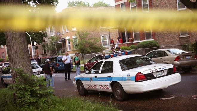 This file photo shows Chicago police investigating a shooting in 2013.