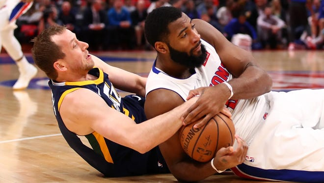 Pistons center Andre Drummond battles on the floor for the ball with Jazz forward Joe Ingles on Wednesday, Jan. 24, 2018, at Little Caesars Arena.