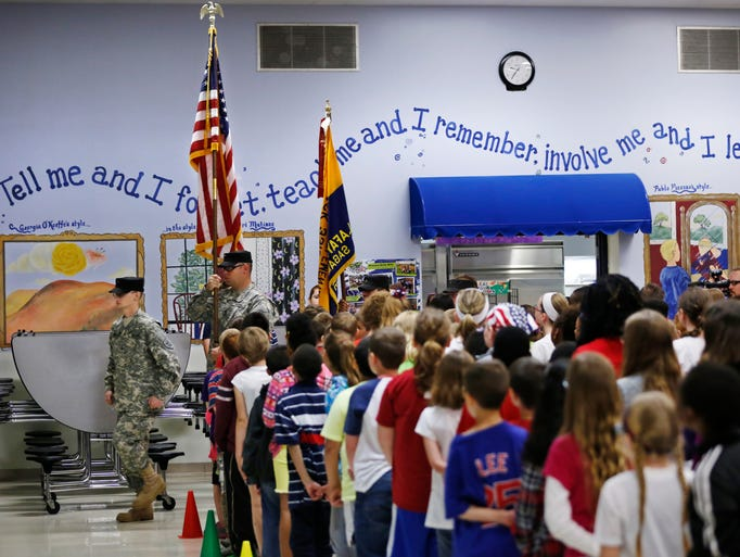 Students stand as a color guard from the Indiana Guard Reserves posts the colors as part of Operation American Pride Friday, May 9, 2014, at Mayflower Mill Elementary School. Mayflower Mill scheduled a day of activities for students to learn about and pay tribute to veterans and members of the military.