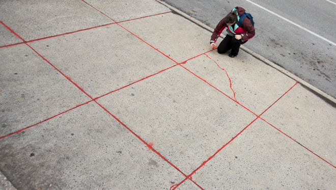 Joanie Wolf, Community and Volunteer Liaison for the YWCA, pours sand into the cracks in the sidewalk on Monday.