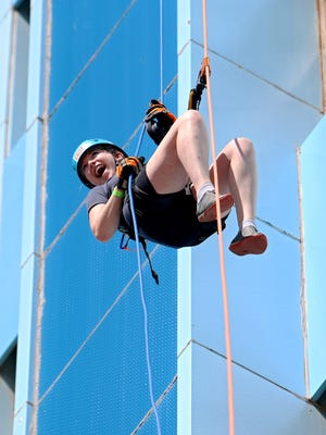Stephanie Seman reacts as she allows herself to briefly free fall while rappelling down the First Wichita Building, or Big Blue, Saturday morning.