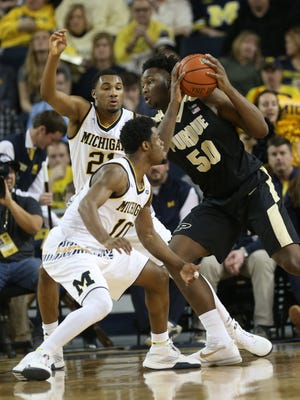 University of Michigan Wolverines Derrick Walton Jr. and Zak Irvin defend against the Purdue Boilermakers Caleb Swanigan during first half action on Saturday, February 13, 2016 at Crisler Center in Ann Arbor.