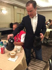 State Attorney General Bill Schuette pours coffee for Michigan delegates to the Republican National Convention as they meet for breakfast Wednesday at their hotel in Cuyahoga Fallls, Ohio, July 20, 2016.