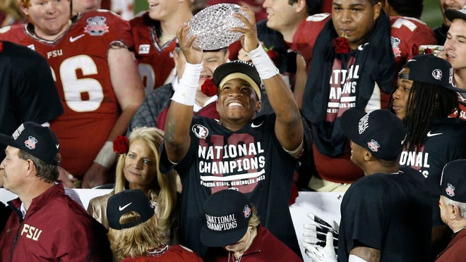Florida State quarterback Jameis Winston celebrates with the championship trophy after the Seminoles beat Auburn to win the 2013 national title.
