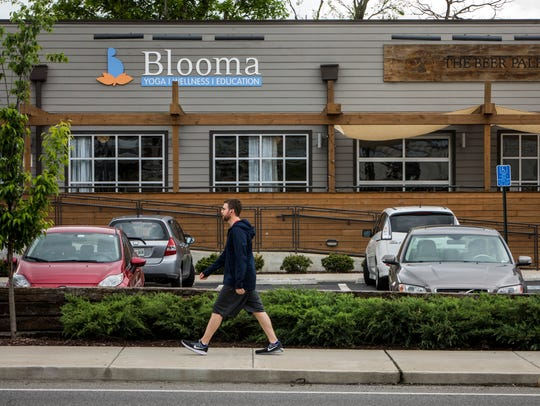 People walk in front of Blooma Yoga Studio and The
