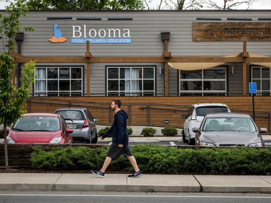 People walk in front of Blooma Yoga Studio and The Beer Pale on Charlotte Avenue. The area has been discovered by buyers and renters, from the apartments at the new Hill Center to nearby neighborhoods like Charlotte Park.