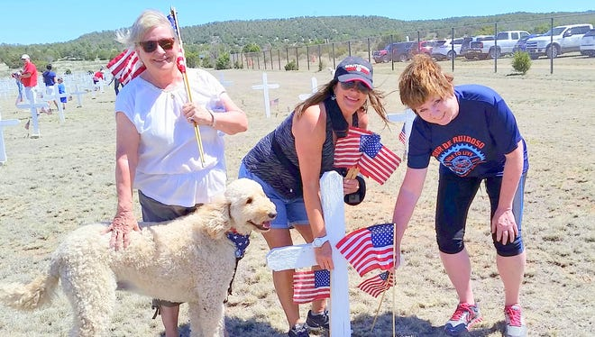 Three volunteers stake their flags while a four-legged friend gives encouragement.