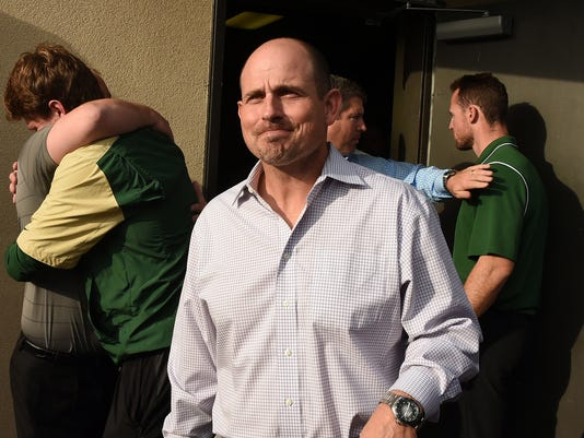 FILE - In this Dec. 2, 2014, file photo, UAB head football coach Bill Clark leaves a meeting with UAB president Ray Watts as players and coaches hug behind him in Birmingham, Ala. Some of the players from UAB's shuttered football program will still get a chance to play together next season, even if it's not with their original school.  (AP Photo/AL.com, Joe Songer, File) MAGS OUT
