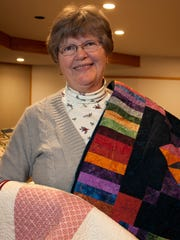 Las Colcheras Quilt Guild member Stephanie Cadena is seen here with her custom designed quilts, Amish With a Twist and Turning Twenty.
