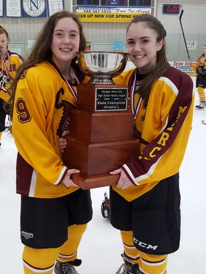 The Bartel sisters from Mercy -- Libby (left) and Ameila -- shared some time with the state championship ice hockey trophy last March.