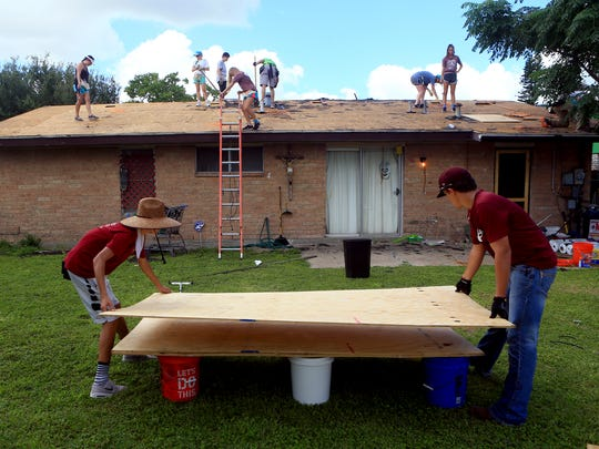 Students from the Sea City Work Camp program remove shingles from a roof as they help repair several homes on Monday, June 12, 2017, in Corpus Christi.