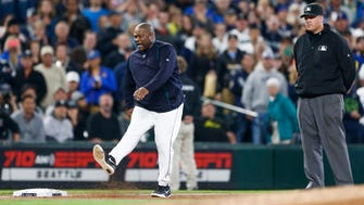 Jun 2, 2015; Seattle, WA, USA; Seattle Mariners manager Lloyd McClendon (23) kicks dirt after being ejected during the third inning against the New York Yankees at Safeco Field. Third base umpire Tony Randazzo (11) stands at right. Mandatory Credit: Joe Nicholson-USA TODAY Sports ORG XMIT: USATSI-214920 ORIG FILE ID:  20150602_ajw_sn8_216.jpg