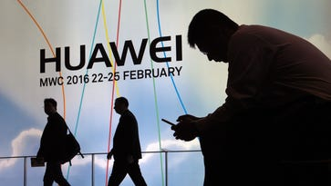 A visitor uses his mobile phone next to the stand of Chinese multinational networking and telecommunications equipment and services company Huawei.