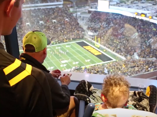 Iowa Hawkeyes football fans wave to children in the hospital