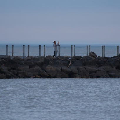 A woman stops to take a photo of Lake Ontario from