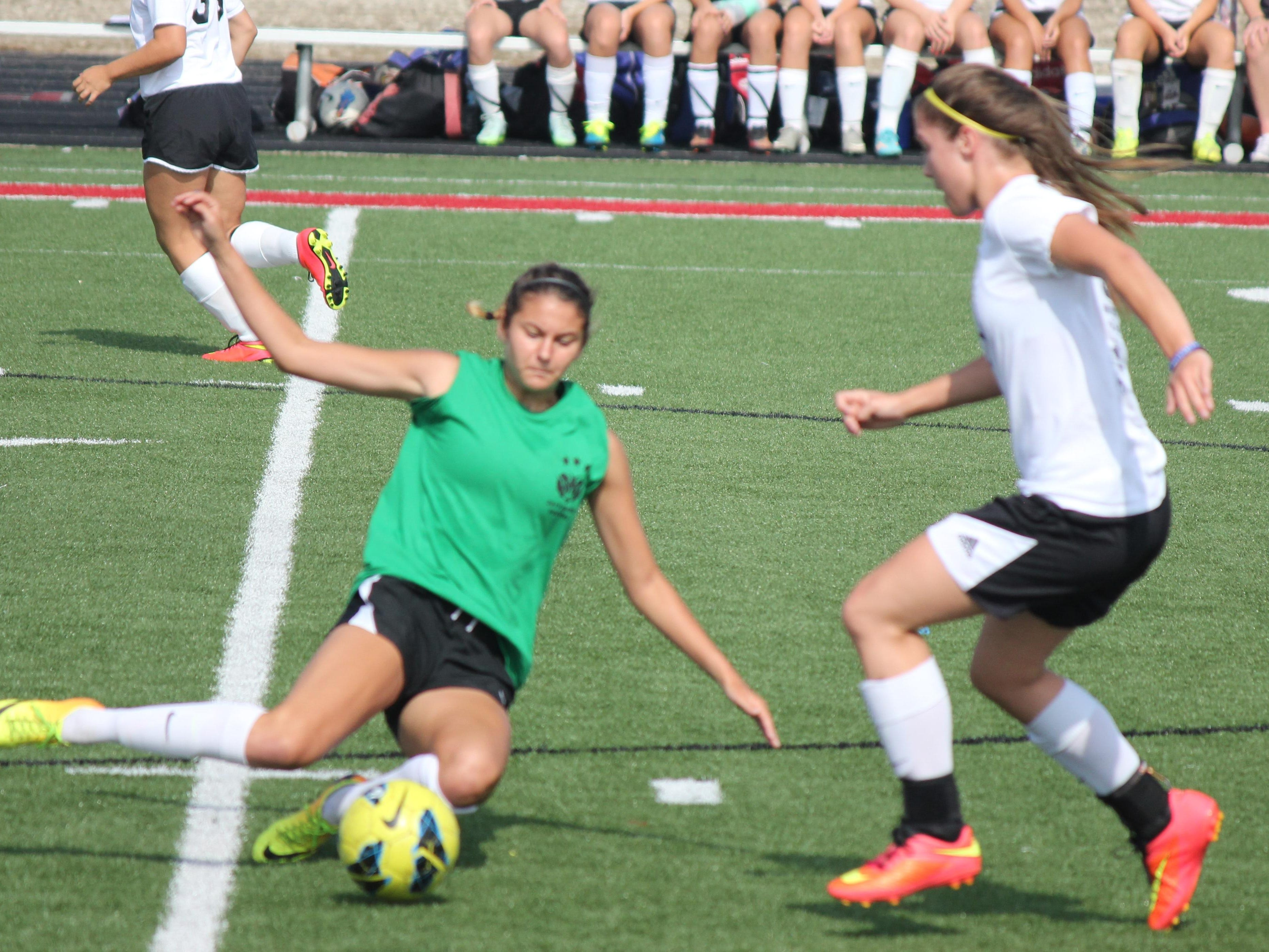 Badin High School's Malia Berkely executes a slide tackle against her McAuley opponent in July 11 scrimmages at Fairfield High School.