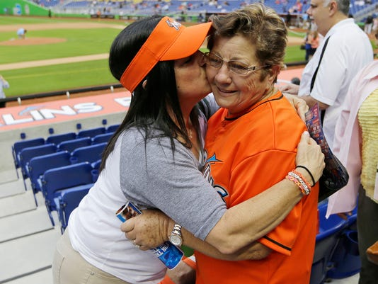 Olga Fernandez, of Cuba, right, gets a kiss from Ana Olga Cairo, left, before an opening day baseball game between the Miami Marlins and Colorado Rockies, Monday, March 31, 2014, in Miami. Olga Fernandez is the grandmother, of starting Marlins pitcher Jose Fernandez, and came from Cuba to see him pitch. (AP Photo/Lynne Sladky)