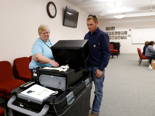 Election clerk Karen Ransom supervises Brandon Milton as he casts his ballot on Tuesday at Bloomfield City Hall.
