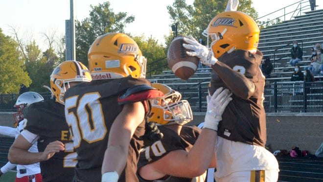 Zeeland East's Cebe Hunderman (right) is mobbed by teammates after scoring on the first offensive play of the game Friday at Zeeland Stadium.