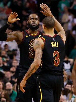 LeBron James and George Hill high five after scoring against the Boston Celtics.