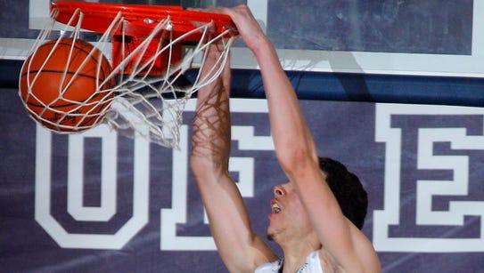 East Lansing's Brandon Johns (23) dunks over Waverly's