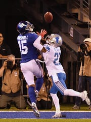 Giants receiver Brandon Marshall goes up for a long touchdown reception but Lions' Darius Slay knocks it away.