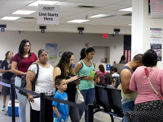 People wait in line at the Arizona Department of Transportation Motor Vehicle Division in Phoenix on June 16, 2016.