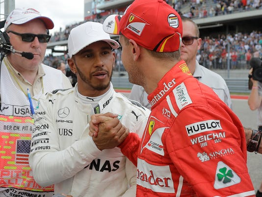 CORRECTS VETTEL TO STARING SECOND, NOT THIRD - Mercedes driver Lewis Hamilton, of Britain, is congratulated by Ferrari driver Sebastian Vettel, of Germany, after Hamilton won the pole during qualifying for the Formula One U.S. Grand Prix auto race at the Circuit of the Americas, Saturday, Oct. 21, 2017, in Austin, Texas. Vettel is starting second. (AP Photo/Darron Cummings)