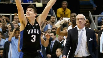 Grayson Allen #3 of the Duke Blue Devils celebrates after defeating the North Carolina Tar Heels 74-73 as head coach Roy Williams watches on during their game at Dean Smith Center.