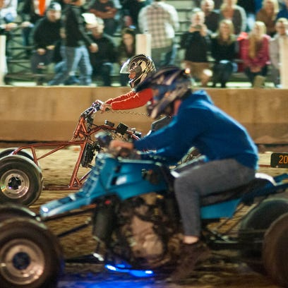 Racers lean back on their four wheelers and run all