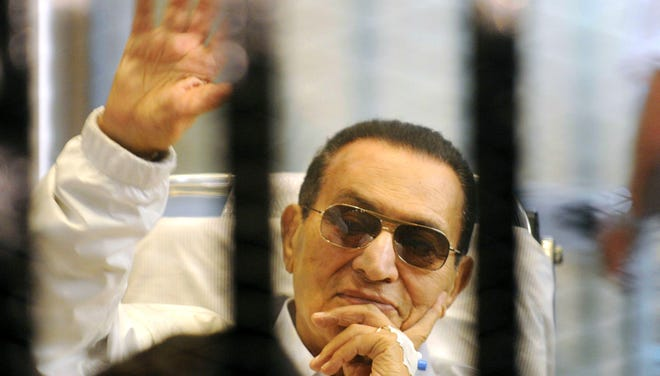 In this April 13 file photo, former Egyptian President Hosni Mubarak waves to his supporters from behind bars as he attends a hearing in his retrial on appeal in Cairo.