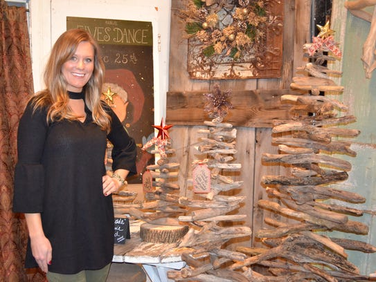Lauren Shaw with her handmade Lake Erie driftwood trees