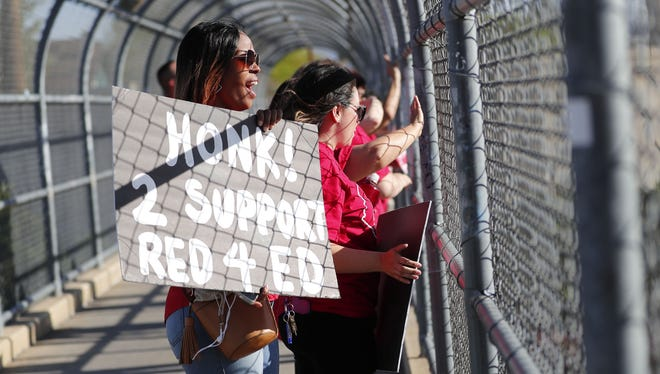 Amica Franks, a 6th grade reading teacher from Garfield Elementary School, holds a sign along with other teachers  at afternoon rush hour traffic from the 10th St. pedestrian bridge over I-10 April 18, 2018.