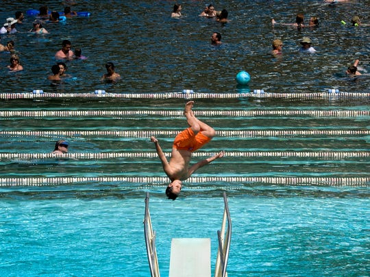 A boy jumps of the diving board at the Glenwood Hot Springs Thursday, July 16, 2015, in Glenwood Springs, CO.