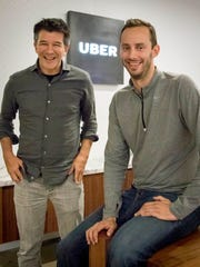 Uber CEO Travis Kalanick, left, and Anthony Levandowski, co-founder of Otto, pose for a photo in the lobby of Uber headquarters, Thursday, Aug. 18, 2016, in San Francisco. Uber announced that it is acquiring self-driving startup Otto, which has developed technology allowing big rigs to drive themselves.